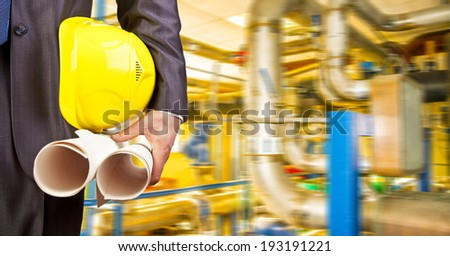 Man working in oil or gas refinery, turning on and off pipeline valve torso and hand engineer yellow holding paper plan, helmet for workers security construction worker No face Unrecognizable person - stock photo