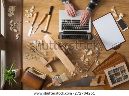 Man working on a DIY project with his laptop, wood shavings and carpentry tools all around, top view - stock photo
