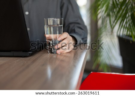 Man Working on a Laptop and Holding a Glass of Water.