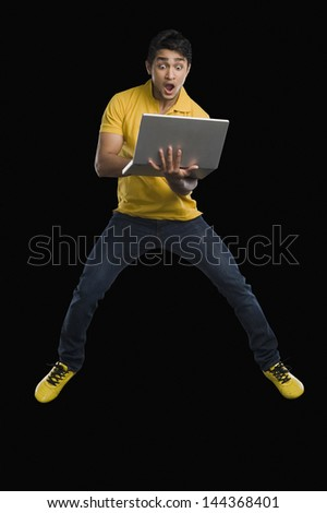 Man working on a laptop and looking surprised - stock photo