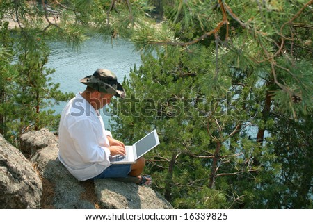 Man working on a laptop on the rocks. With copy space - you can place what you wish on the monitor.