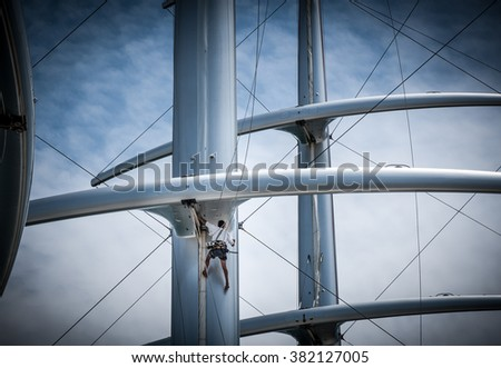 Man working on a modern designed sailboat masts - stock photo