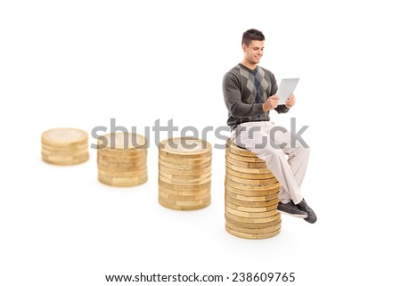Man working on a tablet seated on pile of coins isolated on white background - stock photo