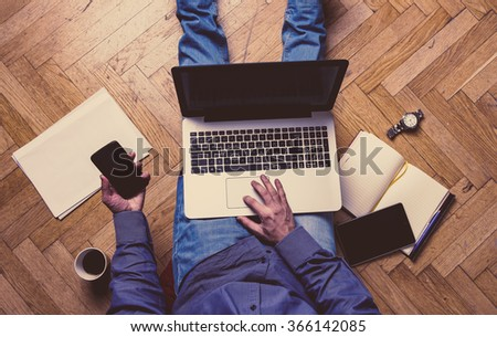 Man working on a wooden floor with his laptop, phone, tablet and agenda. - stock photo