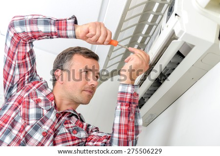 Man working on air conditioning unit, flap open - stock photo
