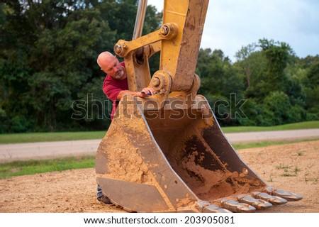 Man working on backhoe bucket - stock photo