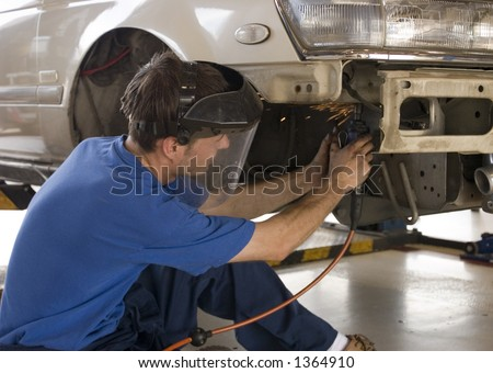 man working on car using safety equipment - stock photo