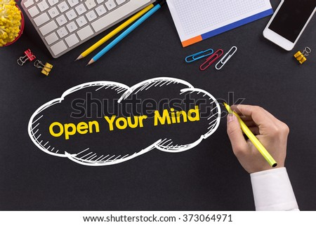 Man working on desk and writing Open Your Mind - stock photo