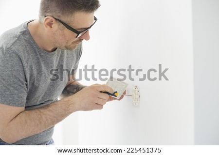 Man working on electrical outlet - stock photo