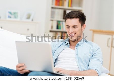 Man working on his laptop at home as he relaxes on a comfortable sofa smiling as he reads the screen - stock photo
