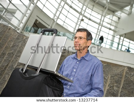 Man working on his laptop computer in Seattle airport terminal, laptop propped on his suitcase - stock photo