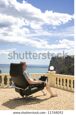 Man Working on his Laptop From Vacation, overlooking blue sea and sky - stock photo