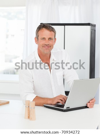 Man working on his laptop in his kitchen - stock photo