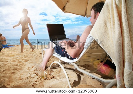 Man working on laptop at tropical beach in Hawaii - stock photo