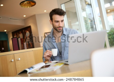 Man working on laptop computer from home - stock photo