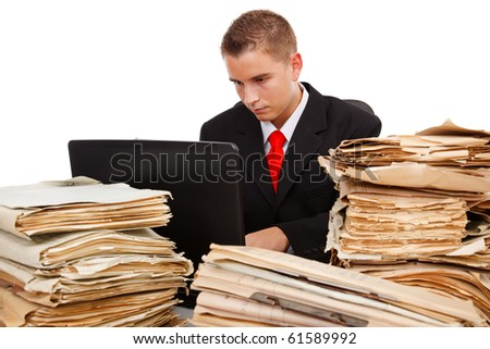 Man working on laptop computer, surrounded with lots of paperwork - stock photo