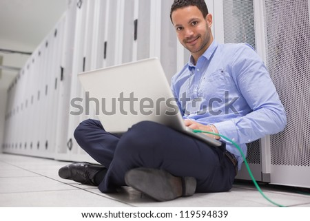 Man working on laptop connected to server in data center - stock photo