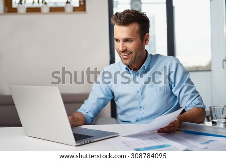 Man working on laptop from home. Counting financial data. - stock photo