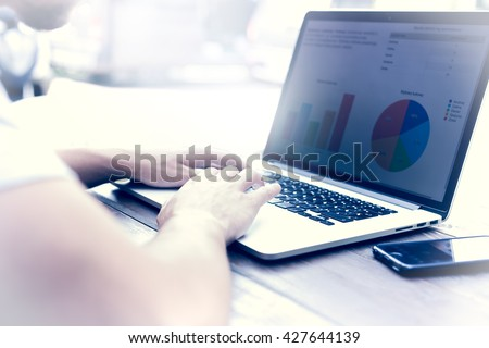 Man working on laptop outside, analysing bussines graphs - stock photo