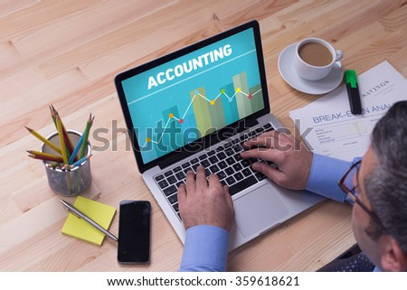 Man working on laptop with ACCOUNTING on a screen - stock photo