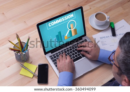Man working on laptop with COMMISSION on a screen - stock photo