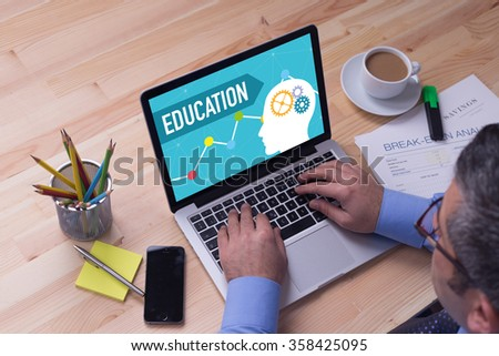 Man working on laptop with EDUCATION on a screen - stock photo