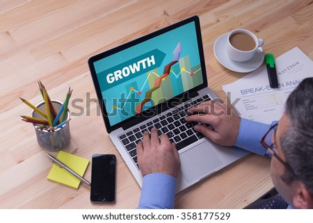 Man working on laptop with GROWTH on a screen - stock photo