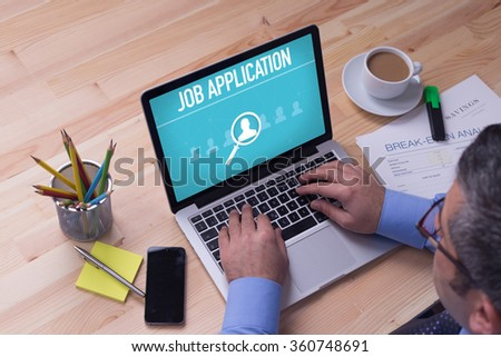 Man working on laptop with JOB APPLICATION on a screen - stock photo