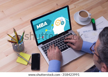 Man working on laptop with MBA on a screen - stock photo