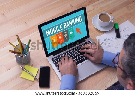 Man working on laptop with MOBILE BANKING on a screen - stock photo