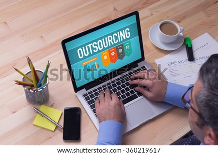 Man working on laptop with OUTSOURCING on a screen