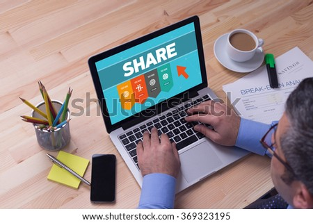 Man working on laptop with SHARE on a screen - stock photo