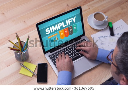 Man working on laptop with SIMPLIFY on a screen - stock photo