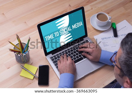 Man working on laptop with TIME TO SOCIAL MEDIA on a screen - stock photo
