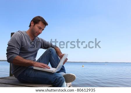 Man working on pier - stock photo