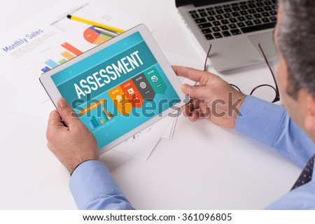 Man working on tablet with ASSESSMENT on a screen - stock photo