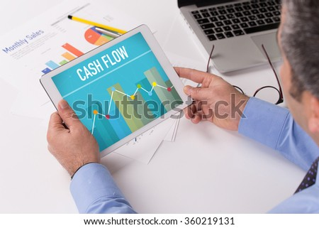 Man working on tablet with CASH FLOW on a screen - stock photo