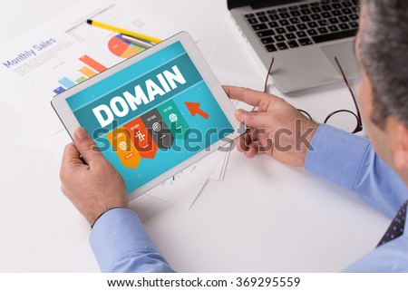 Man working on tablet with DOMAIN on a screen - stock photo