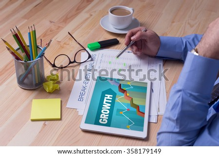 Man working on tablet with GROWTH on a screen - stock photo