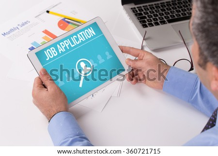 Man working on tablet with JOB APPLICATION on a screen - stock photo