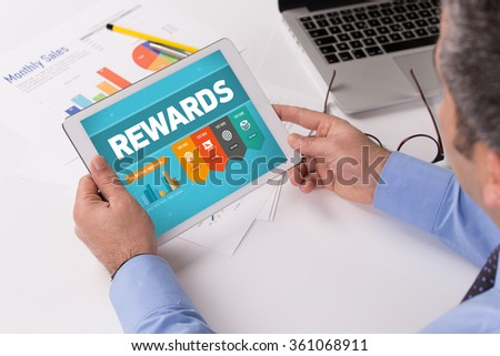 Man working on tablet with REWARDS on a screen - stock photo