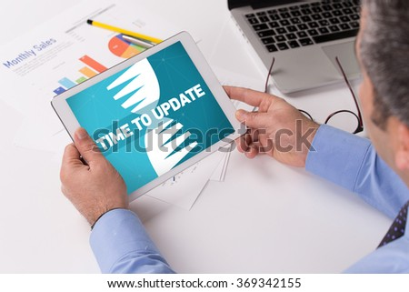 Man working on tablet with TIME TO UPDATE on a screen - stock photo