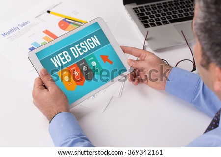 Man working on tablet with WEB DESIGN on a screen - stock photo