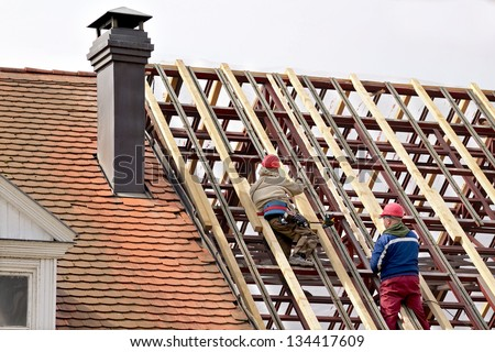 Man working on the new roof - stock photo