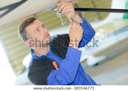 Man working on the underside of an aircraft - stock photo