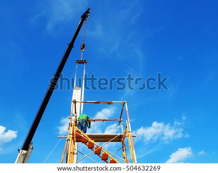 Man Working on the Working at height with blue sky at construction site