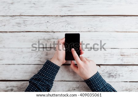 man working or playing with smartphone , hands detail on a wooden office table. the work place on background. business and technology concept. desktop top view, unrecognizable people - stock photo