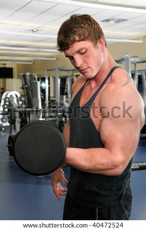 Man working out at gym curling a dumbbell