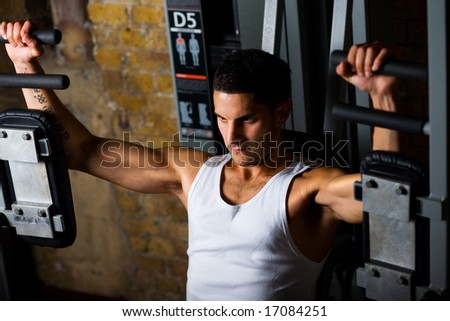 Man working out in gym on pec flye - stock photo