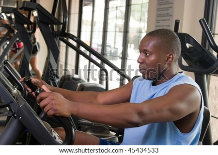 Man working out on a stationary cycle machine in a fitness club. - stock photo